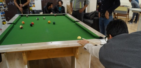 Refugees play pool together